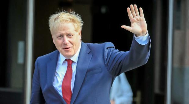 Boris Johnson waves as he arrives at the Conservative Party Conference in Manchester (PA)