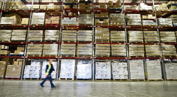 A warehouse worker passes huge racking and pallets of medical supplies (Ben Birchall/PA)