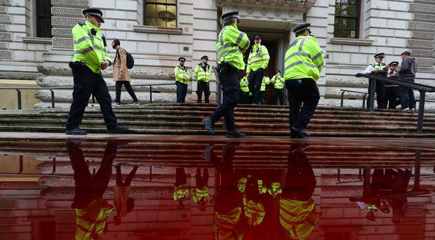 Police officers outside the Treasury building in Westminster, where Extinction Rebellion campaigners sprayed gallons of fake blood (Aaron Chown/PA)