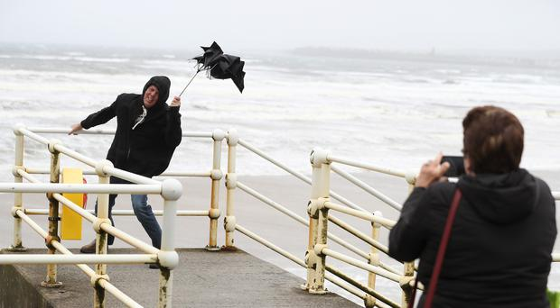 American tourists take photos with a broken umbrella along the sea front in Lahinch, County Clare (Brian Lawless/PA)