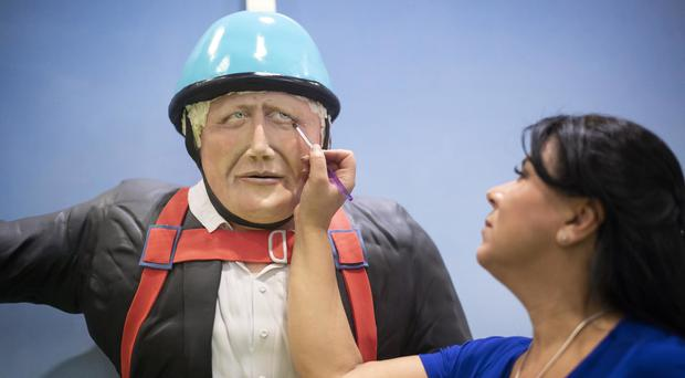 Cake maker Rosie Dummer makes the final touches to a life-sized Boris Johnson cake at the Cake and Bake Show at ExCeL in London (Victoria Jones/PA)