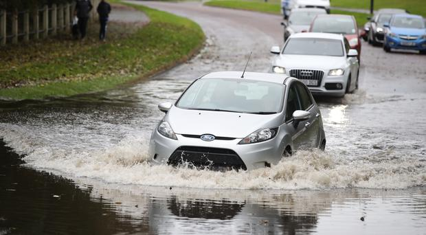 Cars travel through a flooded street in Whitley Bay in Northumberland (Owen Humphreys/PA)