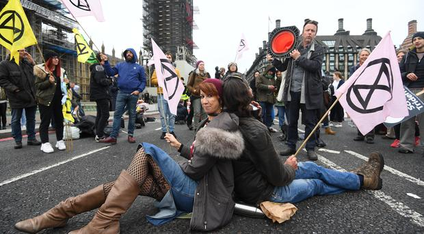 A pair of protesters chained together at the neck on Westminster Bridge, during an Extinction Rebellion (XR) protest in Westminster, London (Victoria Jones/PA)