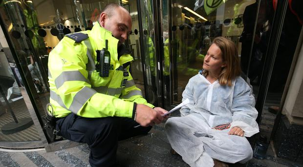 A police officer reads a Section 14 order to a protester who has glued herself to the floor as part of an Extinction Rebellion protest outside the Department for Transport in Horseferry Road, Westminster (Jonathan Brady/PA)