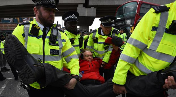 A man is carried away by police, after climate activists staged a demonstration at London City Airport (Kirsty O'Connor/PA)