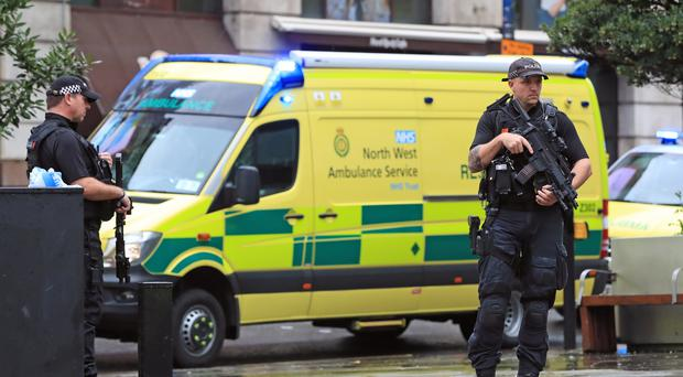 Armed police and ambulances outside the Arndale Centre in Manchester where at least five people have been treated after a stabbing incident (PA)