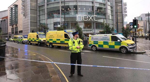 A police officer and ambulances outside the Arndale Centre in Manchester (Peter Byrne/PA)