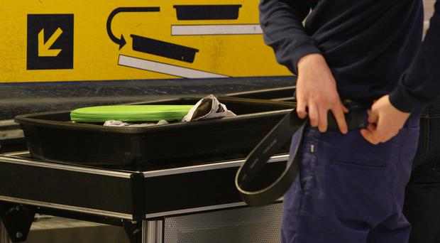 A passenger replaces their belt having passed through security at Manchester Airport (Dave Thompson/PA)