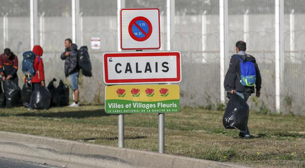 Migrants are moved on from a camp in Calais, France (Steve Parsons/PA)