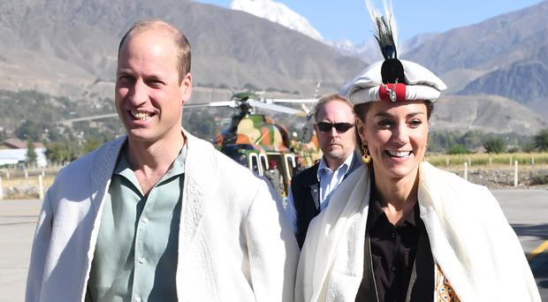 The Duke and Duchess of Cambridge wear a traditional hat and cloak during a visit to a village in the Chitral Valley in Pakistan (Sam Hussein/AP)