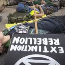 "Extinction Rebellion protesters stage a ""die in"" at Leeds City Centre in Yorkshire (Danny Lawson/PA)"
