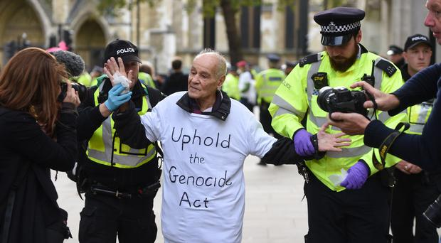 A protester is led away by police outside the Supreme Court (David Mirzoeff/PA)