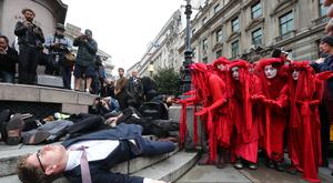 The group known as the Red Rebels joins protesters blocking the road outside Mansion House in the City of London, during a climate change protest (Gareth Fuller/PA)