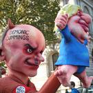 Protesters push a float depicting Dominic Cummings using Prime Minister Boris Johnson as a puppet down Whitehall ahead of an anit-Brexit march in London. (Yui Mok/PA)