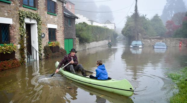 Paul Hayes ferries children to dry land after their family holiday accommodation has been surrounded by floodwater in Lower Lydbrook, where rain from the Welsh hills and high tides have flooded the village, which sits next to the banks of the River Wye, rendering it impassable (PA)