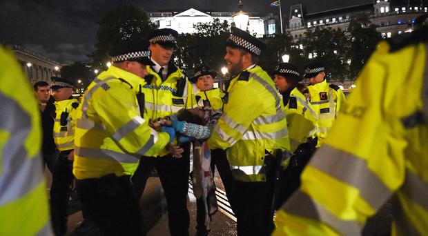 Police remove an Extinction Rebellion protester from Trafalgar Square (David Mirzoeff/PA)