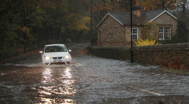 A car passing through a flooded road in Dore, Derbyshire (Danny Lawson/PA)