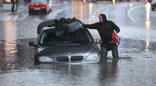 A man with a car in a flooded street in Sheffield (Danny Lawson/PA)
