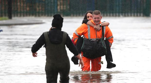 A man in high visibility overalls carries a woman through floodwater in Doncaster (Danny Lawson/PA)