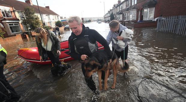 A dog is carried to safety on Yarborough Terrace in Doncaster, Yorkshire, as parts of England endured a month's worth of rain in 24 hours (Danny Lawson/PA)
