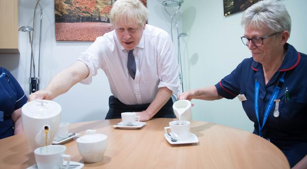 Boris Johnson pours tea as he meets staff and nurses during a visit to King's Mill Hospital in Sutton-in-Ashfield (Stefan Rousseau/PA)