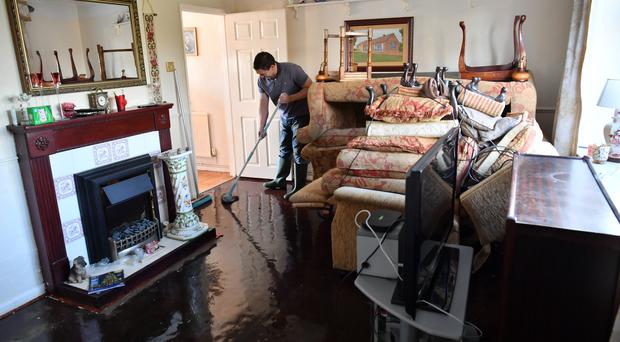 Paul Croucher mops his parents' living room after it was flooded in Fishlake (Ben Birchall/PA)