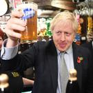 Boris Johnson raises a pint watched by Defence Minister Johnny Mercer (right) as he meets with military veterans at the Lych Gate Tavern in Wolverhampton (Stefan Rousseau/PA)