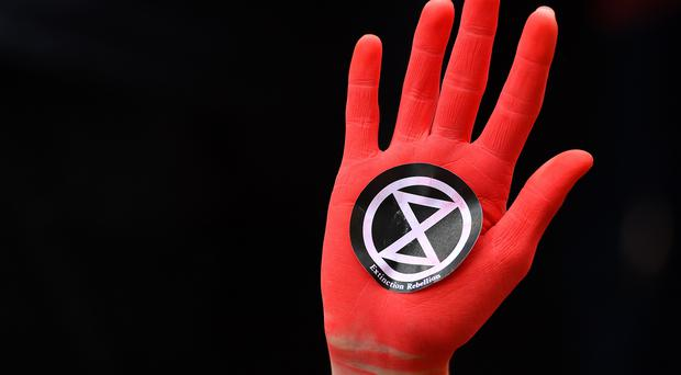 File photo dated 18/10/19 of a protester's hand sprayed red with an Extinction Rebellion (XR) logo stuck on in Westminster, London. High Court judges will rule on the legality of a London-wide police ban on XR protests.