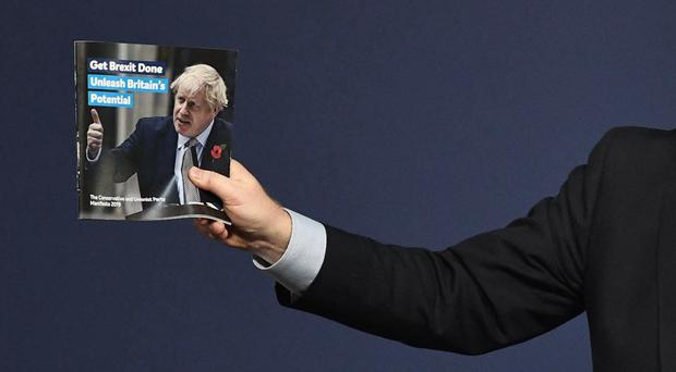 Boris Johnson holds a copy of the Conservative manifesto (Stefan Rousseau/PA)