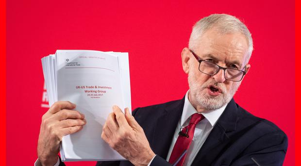 Jeremy Corbyn holds what he said were 'uncensored' papers from US trade talks (Dominic Lipinski/PA)