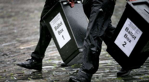 Ballot boxes are carried to a polling station (Jane Barlow/PA)