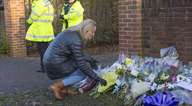 A woman leaves a floral bouquet at the entrance to Debden Park High School, in Willingale Road, Loughton (Rick Findler/PA)