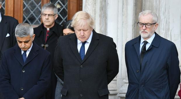 Prime Minister Boris Johnson pays his respects, along with Labour leader Jeremy Corbyn and London Mayor Sadiq Khan at a vigil to the two people killed in the Fishmongers' Hall terror attack (Dominic Lipinski/PA)
