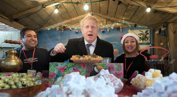 Prime Minister Boris Johnson at a stall selling Turkish delight during a walkabout at a Christmas Market in Salisbury (Stefan Rousseau/PA)