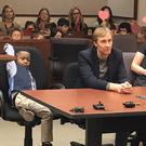 Michael with his class behind him at an adoption hearing (Kent County/PA)