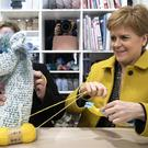 SNP leader Nicola Sturgeon makes pom-poms with SNP candidate Kirsten Oswald (Jane Barlow/PA)