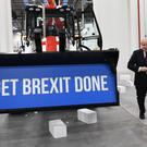 Prime Minister Boris Johnson walks away after driving a Union flag-themed JCB, with the words 'Get Brexit Done' inside the digger bucket (Stefan Rousseau/PA)