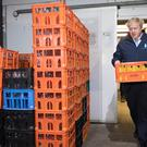 Prime Minister Boris Johnson carries a crate into a delivery van during a visit to Greenside Farm Business Park in Leeds (Stefan Rousseau/PA)