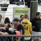 Families of victims of the White Island eruption embrace as they arrive back at the Whakatane wharf following a blessing at sea (Mark Baker/AP)