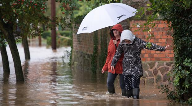 Local residents make their way through floodwater in Cossington, Leicester (Joe Giddens/PA)