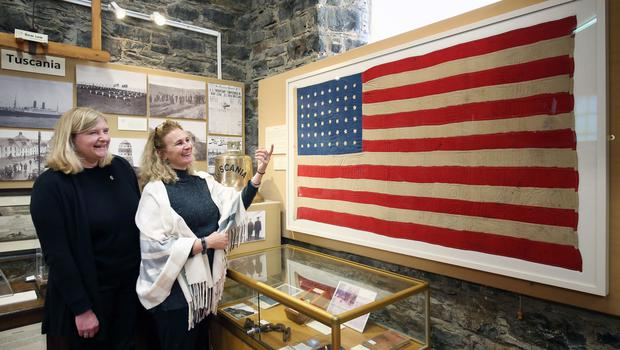 Jenni Minto, from the Museum of Islay Life (left) and Jennifer Jones from the Smithsonian Museum in Washington DC alongside the flag made 100 years ago on the island of Islay for the US crew members who lost their lives in the SS Tuscania disaster (Jane Barlow/PA)