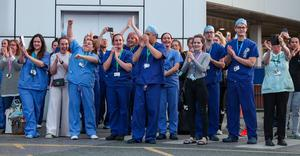 NHS workers at Royal Liverpool University Hospital come outside to see the public clapping to salute local heroes during Thursday's nationwide Clap for Carers (Peter Byrne/PA)