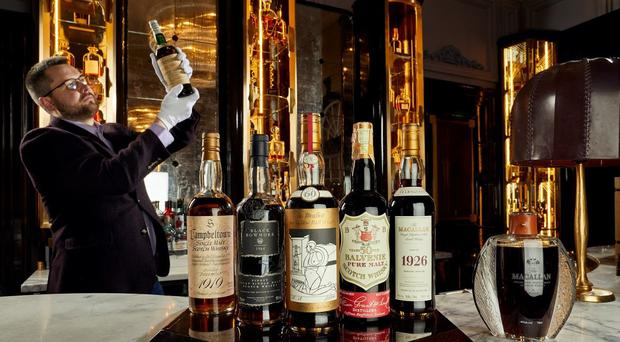 Whisky Auctioneer founder Iain McClune examines some of the collection (Peter Dibdin/Spey/PA)