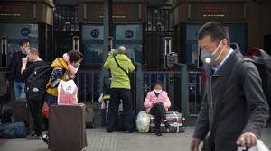 Travellers wearing face masks walk outside the Beijing Railway Station in Beijing on March 25, 2020. A British teacher living in China has called on the UK to adopt similar measures to the Chinese government to tackle the outbreak (AP Photo/Mark Schiefelbein).