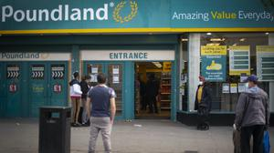Shoppers observe social distancing as they queue to enter a Poundland shop in East Ham, east London (Victoria Jones/PA)