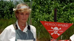 Diana, Princess of Wales wears a protective mask and jacket as she stands next to a warning sign on the edge of a minefield in Angola in 1997 (John Stillwell/PA)