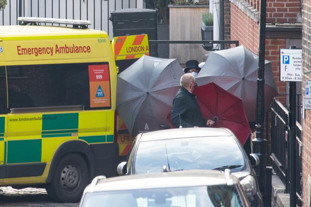 Staff shield the exit with umbrellas alongside an ambulance outside the rear of King Edward VII's Hospital in London where the Duke of Edinburgh was admitted on the evening of Tuesday, February 16 (Dominic Lipinski/PA)