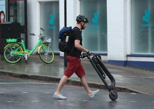 An e-scooter rider pushes his scooter after being stopped by a police officer (Yui Mok/PA)