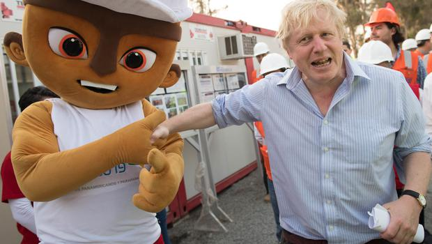 Boris Johnson meets the mascot of the 2019 PanAmerican Games at the athletes' village in Lima, Peru, which is being built with help from UK construction firms (Stefan Rousseau/PA)