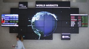 A city worker walks past a stock ticker screen at the London Stock Exchange in the City of London.